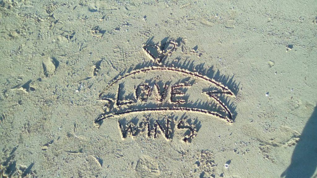 Love wins — desen în nisip